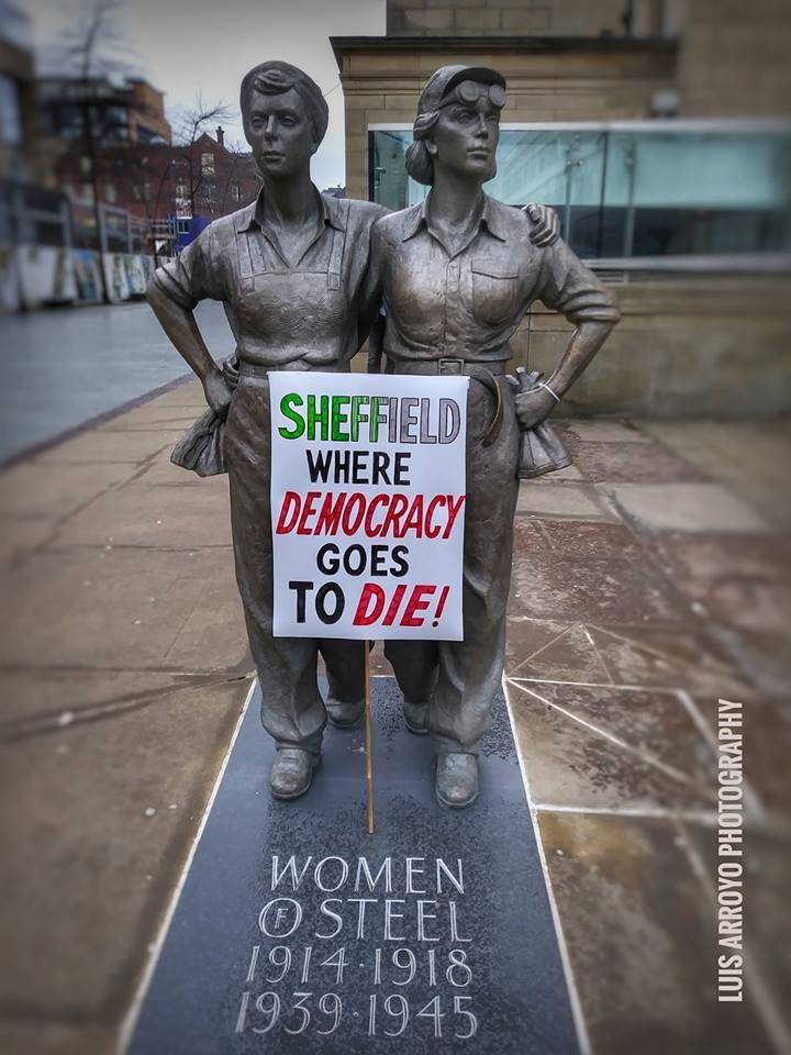 "Women of Steel statue with placard saying ""Sheffield, where democracy goes to die!"""